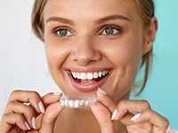 Smiling woman placing Invisalign tray