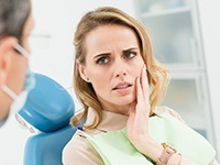Woman in dental chair frowning and holding jaw