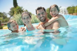 family of four swimming in a pool