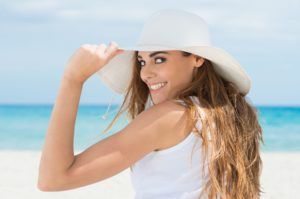woman on the beach smiling after seeing cosmetic dentist in Midlothian, TX