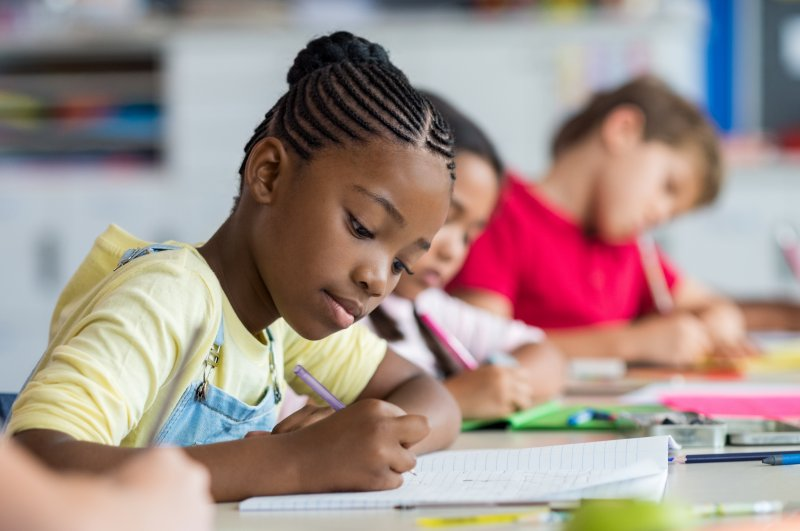 Closeup of girl taking a test in classroom
